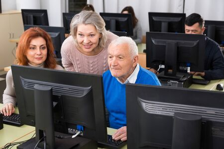 Smiling adult students of different ages looking together at monitor during computer classes at university of third age