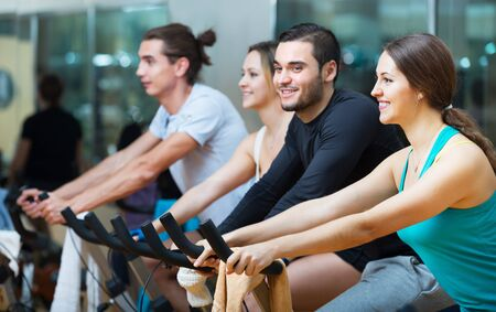 Active adults riding a stationary bicycles in fitness club Banque d'images