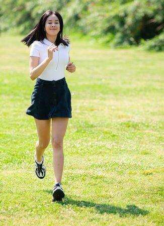 Teen girl runs on a green lawn in the park