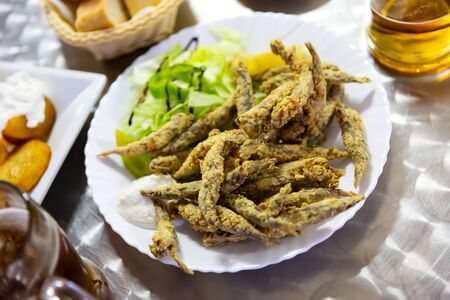Portion of fried anchovies served with greens, lemon and white creamy sauce