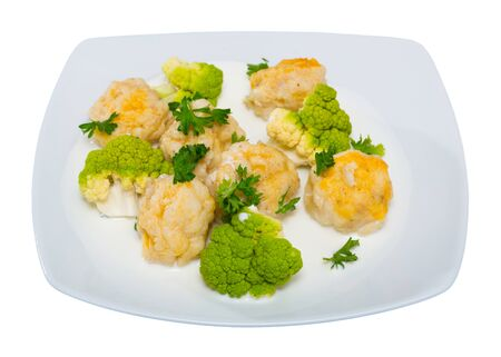 Cod fish croquettes baked in oven served with steamed broccoli. Isolated over white background