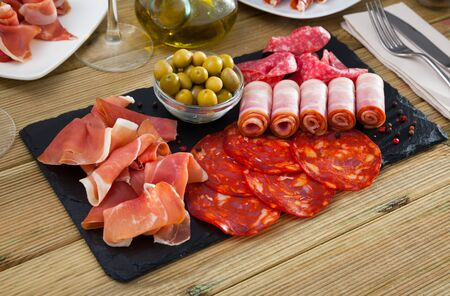 Appetizing cold cuts from Spanish ham, bacon, spicy dry-cured sausages with olives on slate plate