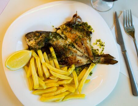 Baked in oven dorado fish with lemon and french fries served on plate
