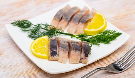 Mediterranean herring fillet served with sliced lemon and dill