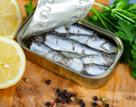 Canned sea fish. Preserved sardines in oil served with herbs and lemon on wooden table Stok Fotoğraf