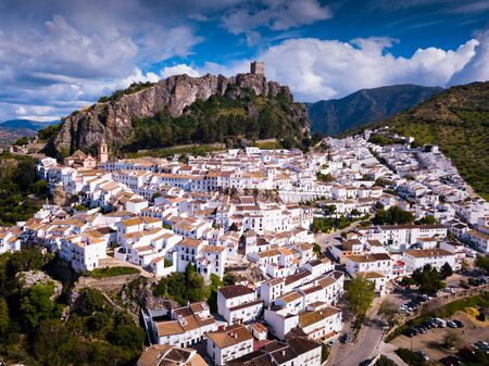 Picturesque aerial view of snow white houses of Zahara de la Sierra on background with ancient castle on rocky hilltop, Spain