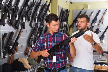 Positive young men choosing air weapon in military store