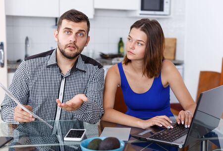 Serious young man and woman with financial documents near laptop at home Reklamní fotografie