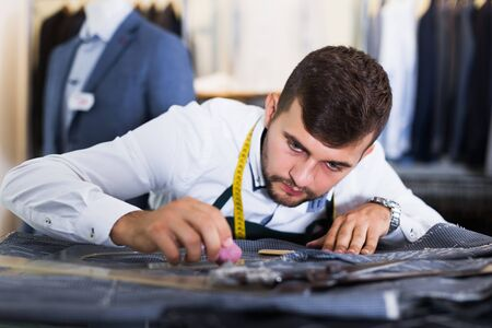 portrait of young concentrated handsome guy snipper  in modern workshop Stock Photo