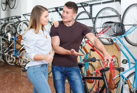 female and male is choosing modern bicycle together in the bike store.