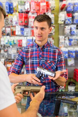 Cheerful young salesman helping customer to choice air gun in airsoft store Stock Photo
