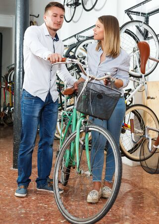 Couple is shopping and choosing new bicycle in bike store.