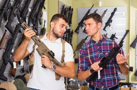 Two young men selecting pneumatic weapon in military shop Imagens