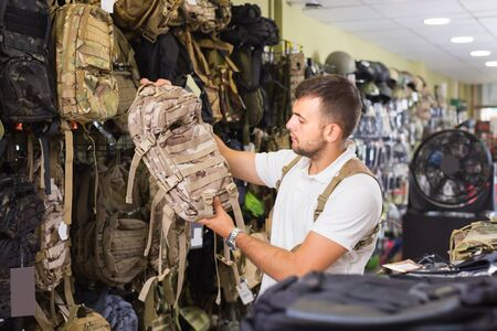positive spanish  man choosing textile backpack gun in military shop Stock Photo