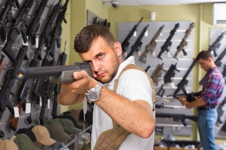 Portrait of young male which is choosing air-powered gun in army market.