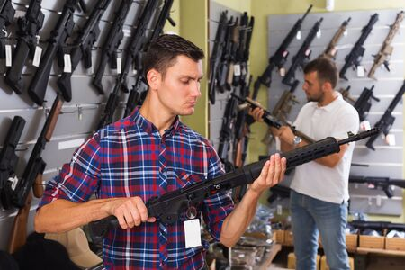 Positive young men choosing air gun in military shop