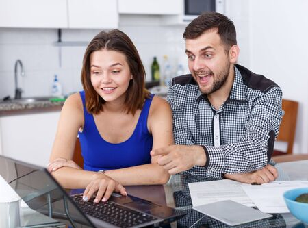 Portrait of young man and woman  looking at laptop  at home interior