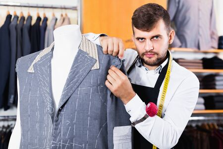 Happy cheerful  smiling handsome male tailor  working  in atelier