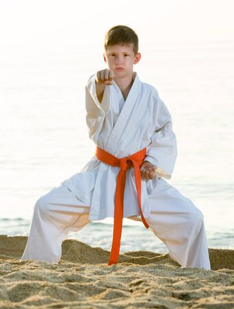 Active little boy doing karate poses at  sunset sea shore Stockfoto