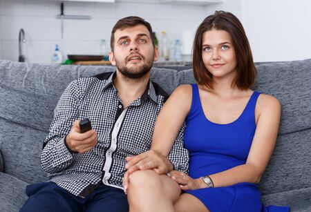 Positive young man and woman sitting on sofa at home watching TV