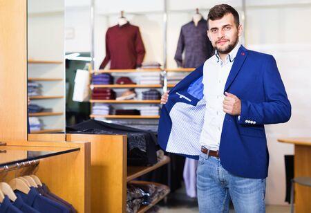 Cheerful positive smiling handsome adult guy choosing modern jacket in men store