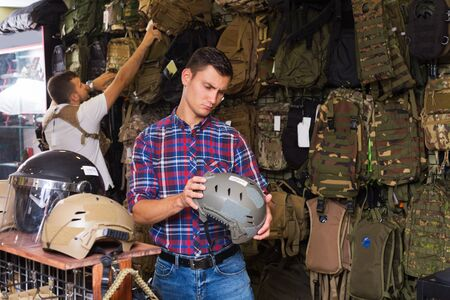 Young serious men choosing helmet in army shop