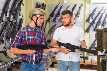 Male 20-30 years old are choosing pneumatic rifle in airsoft store. Stock Photo