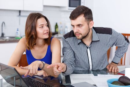 Portrait of a young family couple  looking at laptop at kitchen table