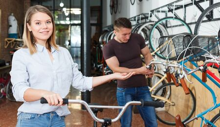 Smiling woman is standing satisfied with bicylce in the bike store.