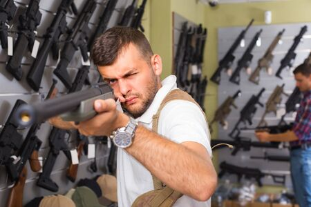 Portrait of male customer which is choosing air-powered gun in army market. Stock Photo