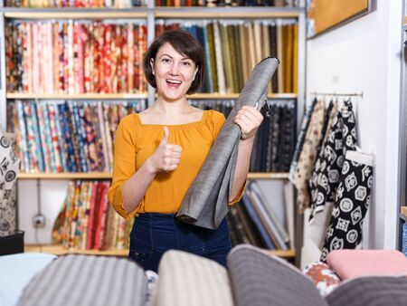 Cheerful woman standing in interior of tissue store, showing thumbs up