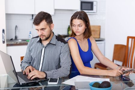 Young man working at laptop and upset girl using phone at home interior