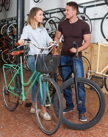 Man with woman are talking about new bicycles in the bike store