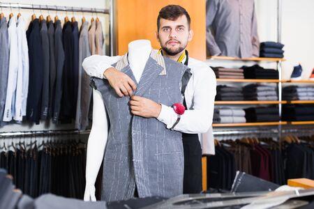 positive handsome   tailor  working  in atelier