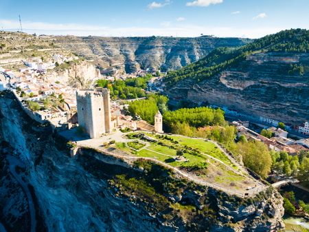 Picturesque landscape with small Spanish town of Alcala del Jucar atop sandstone ridge