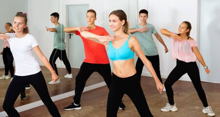 Cheerful positive smiling teenage dancers practicing active vigorous dance in modern studio