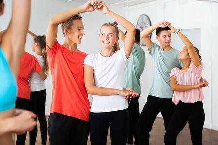Blije tieners in paren die wals leren dansen met jonge vrouwelijke choreograaf in moderne studio