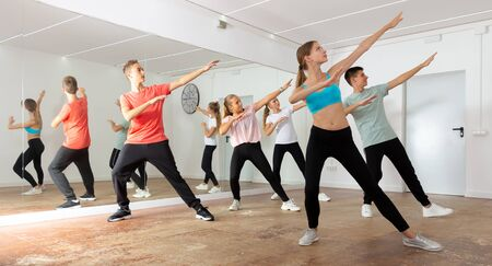 Teenage boys and girls dancing synchronous group choreography in dance hall