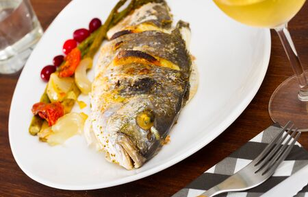 Sea bream baked in oven served with asparagus, onion and tomatoes