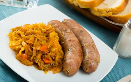 Appetizing meat sausages served with braised cabbage on white plate