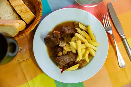 Top view of traditional Asturian dish of stewed beef in rustic style with gravy and french fries Stock Photo