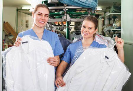 Zwei selbstbewusste lächelnde Mädchenarbeiterinnen, die professionelle chemische Reinigung anbieten und saubere Kleidung zeigen Standard-Bild