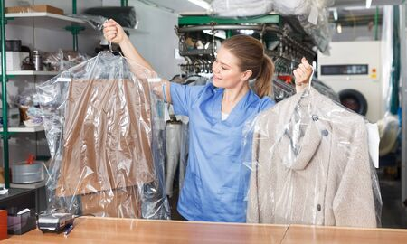 Young woman worker of laundry holding clean garment, demonstrating quality of dry cleaning