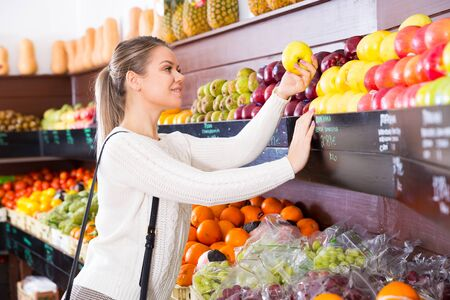 Portrait of cheerful female customer taking fresh fruits on the supermarket