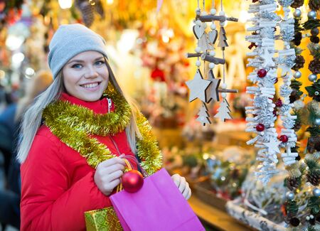 Attractive young woman choosing wooden garland on outdoor Christmas market