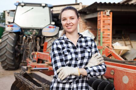 Portrait of young female farmer standing near agricultural machinery on farm