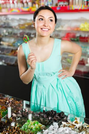 Pretty sexy female posing in the store with lolly on the background of counters with sweets