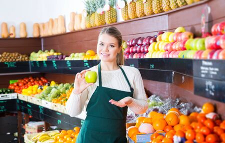 woman selling fresh apples and other fruits on the supermarket Imagens