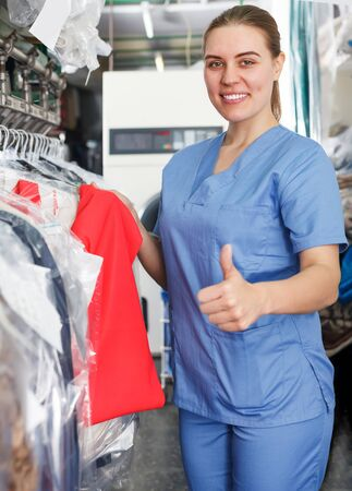 Glad female worker of laundry inspecting clothing after dry cleaning on racks