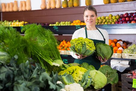 Young woman selling vegetables in greengrocery, offering fresh cabbage Reklamní fotografie